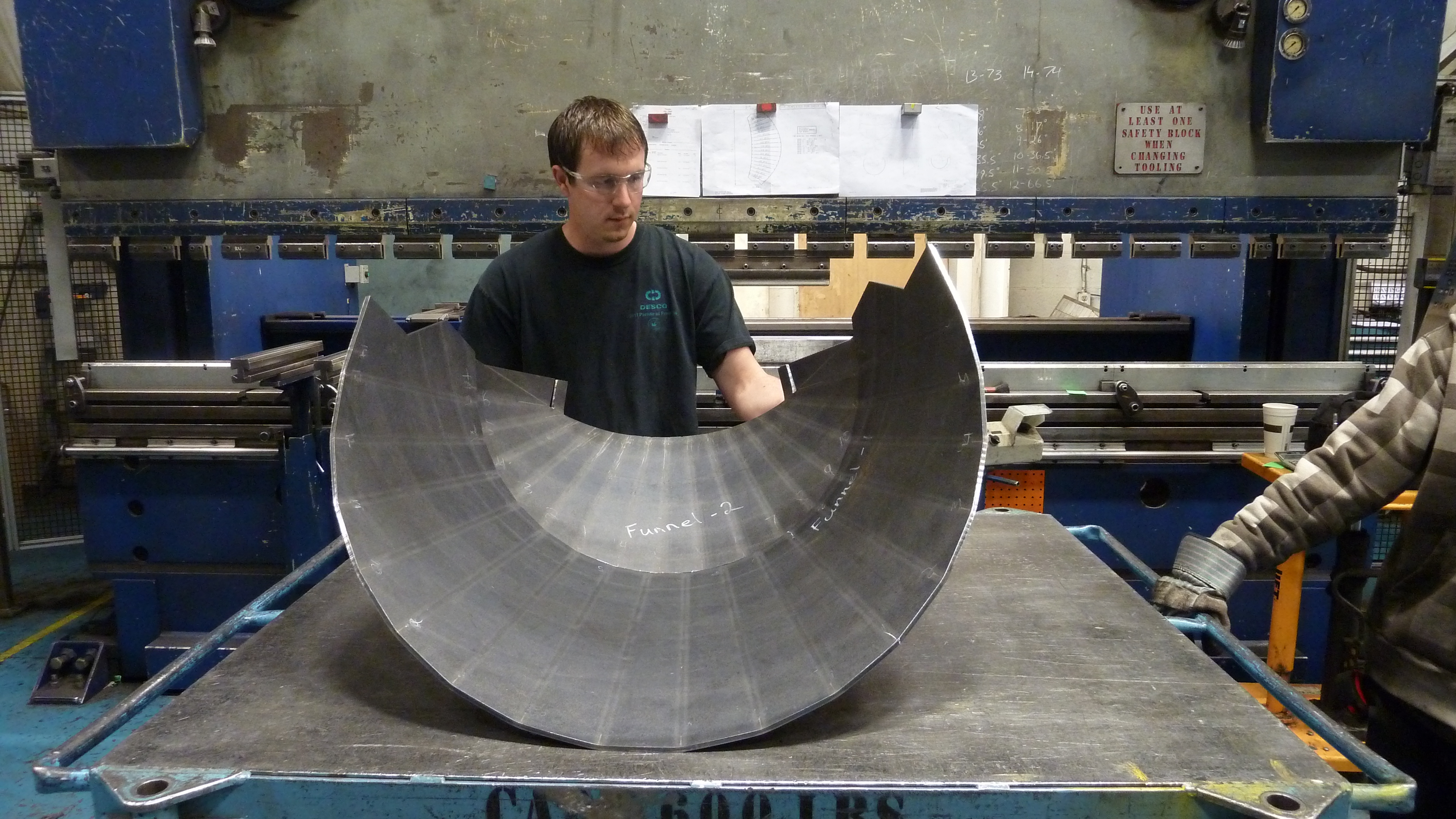 Employee checking fit up of 2 different cone sections rolled for an oven used in the steel mills.