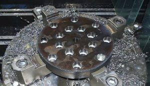 This 2 inch thick round plate shows drilling, tapping and counterboring all in 1 setup which would not be possible on a lathe.