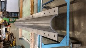 20 foot long part that looks rolled but in fact was step formed on a brake press at VeriForm. This is a communication tower stiffening clamp to help in high ice conditions to reinforce older towers. Part was made from 3/8 inch structural plate.