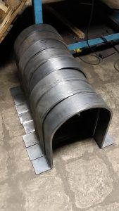 Small flatbar clamps rolled from half inch steel plate and also a bend at each end. The units are about 1 foot high with a 6 inch radius.