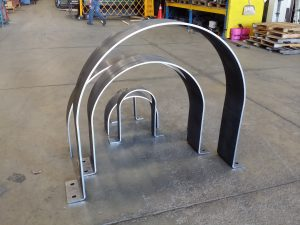 Excellent example of small to large 180 degree rolled sections from 1/2 inch steel plate with holes and then 90 degree bends to make clamping structures for a very large project in the gas sector.
